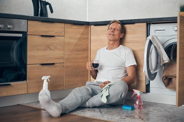 Homem maduro feliz e encantado mantendo os olhos fechados enquanto está sentado no chão da cozinha com uma bebida quente