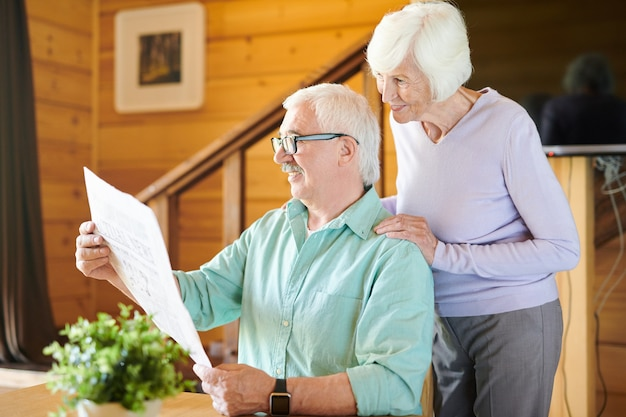 Homem maduro feliz e sua esposa lendo as últimas notícias no jornal pela manhã após o café da manhã