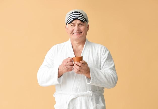 Homem maduro feliz em roupão de banho, com máscara de dormir e xícara de café na parede colorida