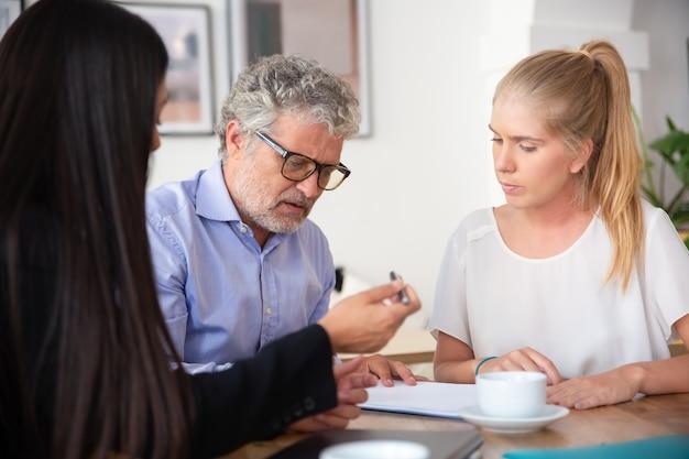 Homem maduro focado lendo documento, sua colega dando uma caneta para ele assinar