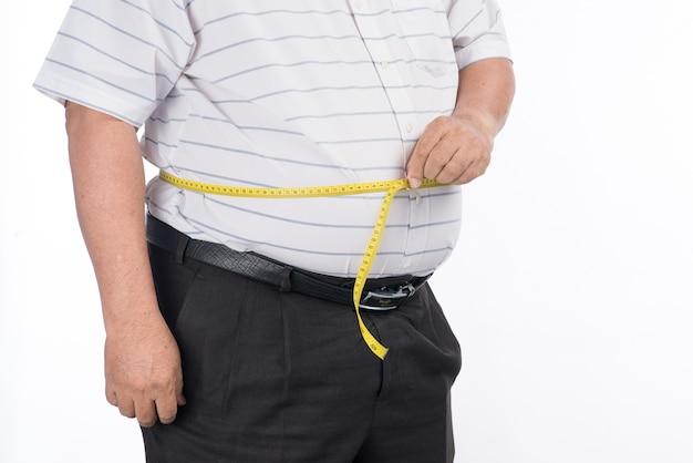 Homem maduro gordo medindo a barriga com fita métrica, isolado no fundo branco