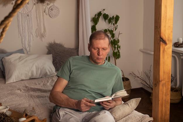 Homem maduro lendo livro no interior aconchegante na moda moderno com planta à noite, sozinho.