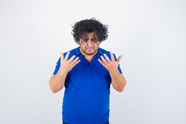 Homem maduro, levantando as mãos em um gesto perplexo em t-shirt azul e olhando melancólico, vista frontal.