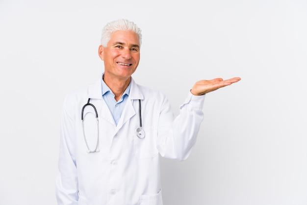 Homem maduro médico caucasiano mostrando um espaço de cópia na palma da mão e segurando a outra mão na cintura.