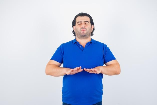 Homem maduro meditando, mantendo os olhos fechados em camiseta azul, jeans e parecendo calmo