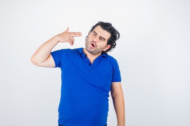 Homem maduro, mostrando gesto de suicídio em camiseta azul e olhando pensativo. vista frontal.