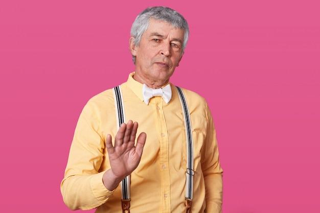Homem maduro na camisa amarela, suspensórios e gravata borboleta branca mostrando sinal de stop com a mão.