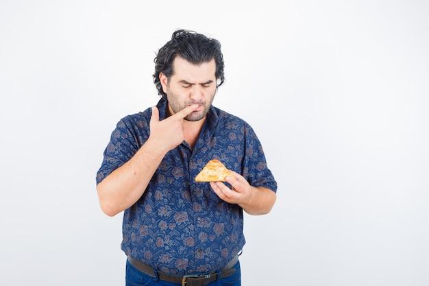 Homem maduro na camisa, olhando para o produto de pastelaria, mantendo o dedo na boca e olhando pensativo, vista frontal.