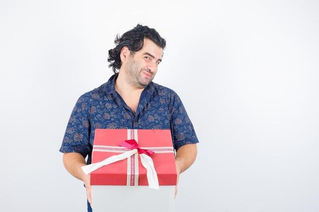Homem maduro na camisa, segurando a caixa de presente e olhando bonito, vista frontal.