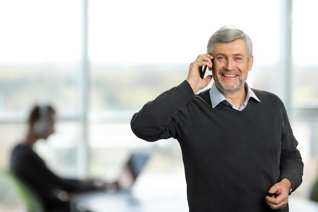 Homem maduro no escritório. homem feliz com cabelos grisalhos, falando no telefone, no escritório. homem sênior sorridente com telefone celular