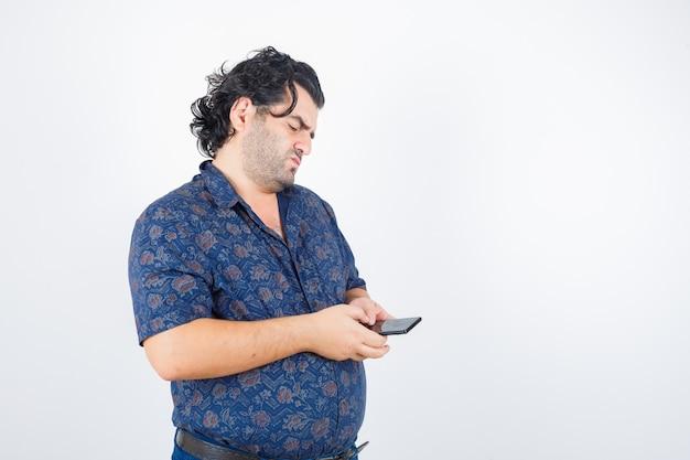 Homem maduro, olhando para o celular em camisa e olhando pensativo, vista frontal.