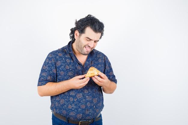 Homem maduro, olhando para o produto de pastelaria na camisa e olhando feliz, vista frontal.