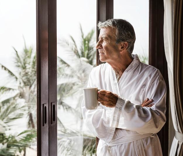 Homem maduro, olhando pela janela do hotel