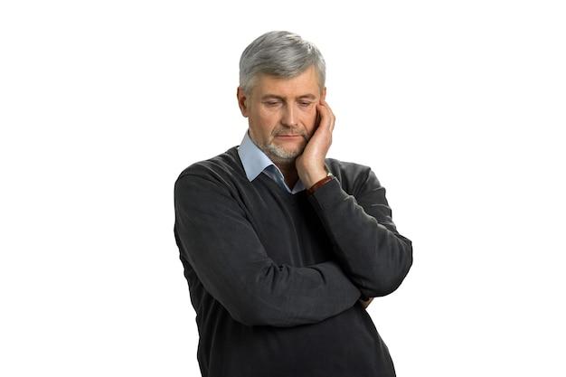 Homem maduro preocupado em branco. homem sênior chateado com olhos baixos pensando contra o branco