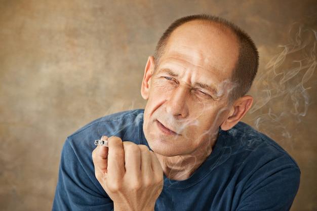 Homem maduro preocupado fumando
