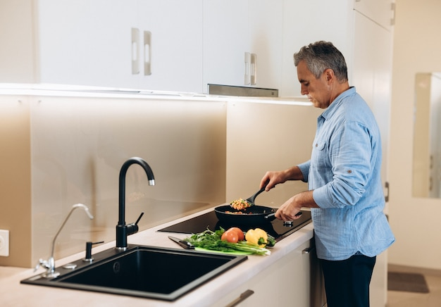 Homem maduro preparando comida saudável para o jantar de sua família