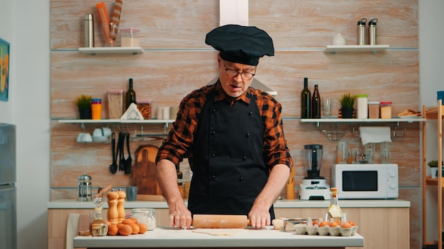 Homem maduro, preparando pizza caseira na cozinha de casa. feliz chef idoso com bonete usando rolo de madeira, amassando ingredientes crus para assar biscoitos tradicionais, polvilhar, peneirar farinha na mesa.