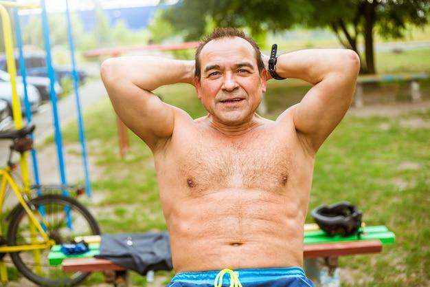 Homem maduro que faz exercícios físicos em uma rua da cidade. o homem sênior bombeia os músculos abdominais, abs.