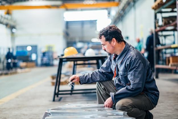 Homem maduro que trabalha com o instrumento de medição na fábrica.