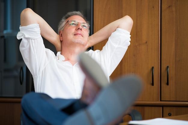 Homem maduro relaxando em seu escritório depois do trabalho