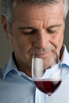 Homem maduro satisfeito cheira uma taça de vinho tinto enquanto a prova