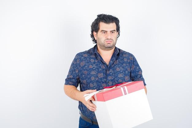 Homem maduro, segurando a caixa de presente enquanto desvia o olhar na camisa e parece pensativo. vista frontal.