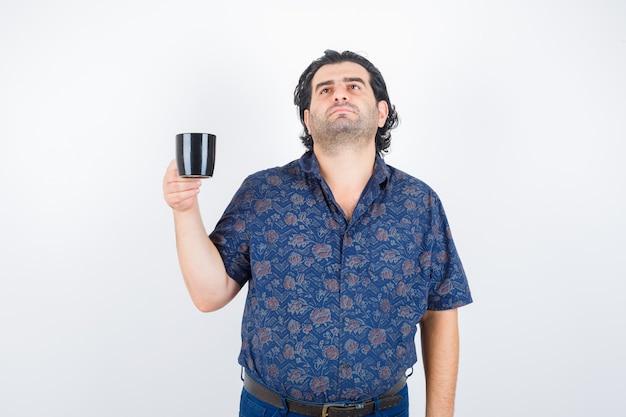 Homem maduro, segurando a xícara enquanto olha para cima na camisa e olhando pensativo, vista frontal.