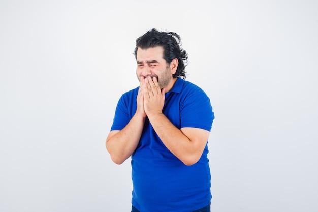 Homem maduro, segurando as mãos na boca em t-shirt azul e parecendo triste. vista frontal.