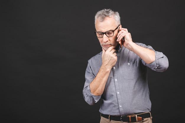 Homem maduro sênior de negócios sérios com roupa formal usando gesto de smartphone