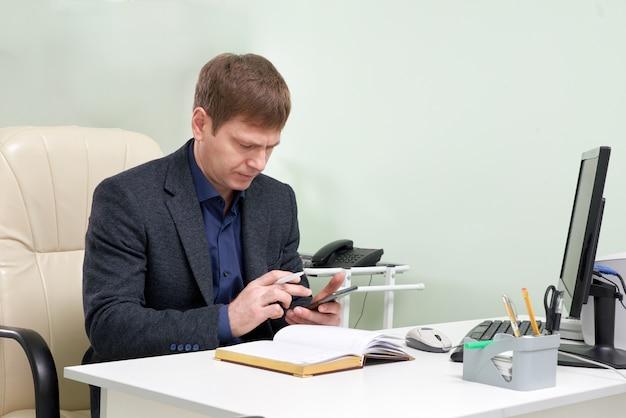 Homem maduro, sentado em suas mensagens de texto de telefone inteligente