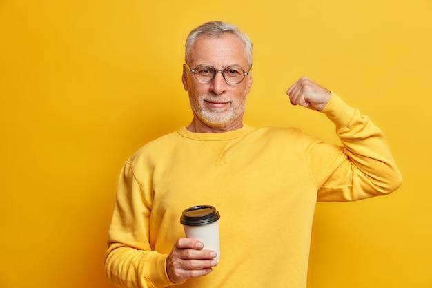 Homem maduro sério e autoconfiante levanta o braço e mostra os bíceps sendo fortes e poderosos segurando um copo de café de papel e usa um macacão casual isolado sobre a parede amarela