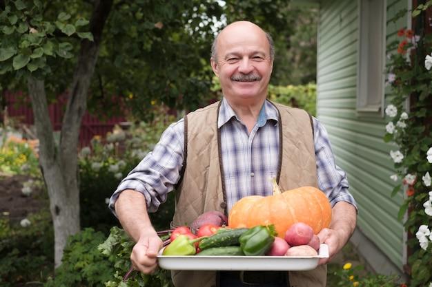 Homem maduro sorridente com legumes colhidos em seu jardim.
