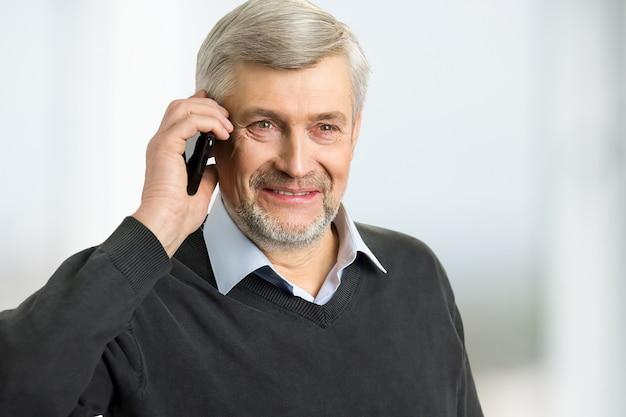 Homem maduro sorridente com telefone. retrato de homem de cabelo grisalho segurando o telefone perto da orelha close-up.