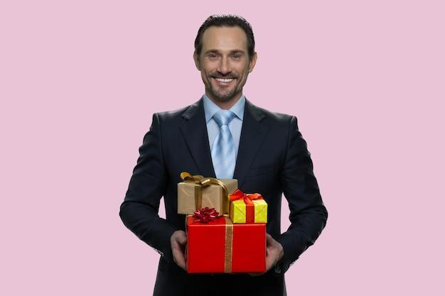 Homem maduro sorridente em um terno formal, segurando caixas de presente. presentes de natal ou aniversário. isolado em fundo rosa.