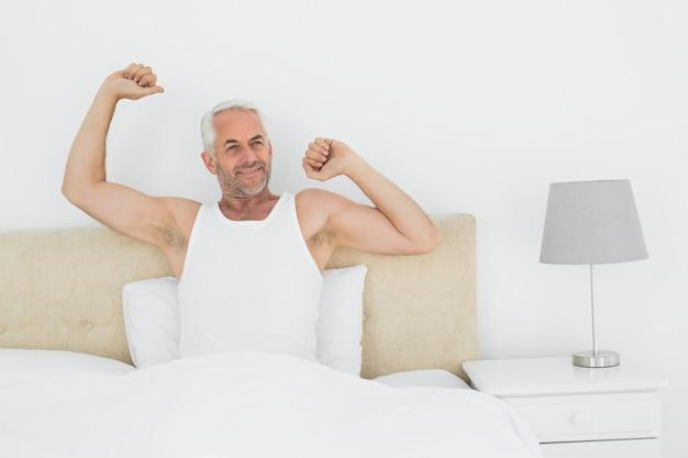 Homem maduro sorridente, esticando os braços na cama