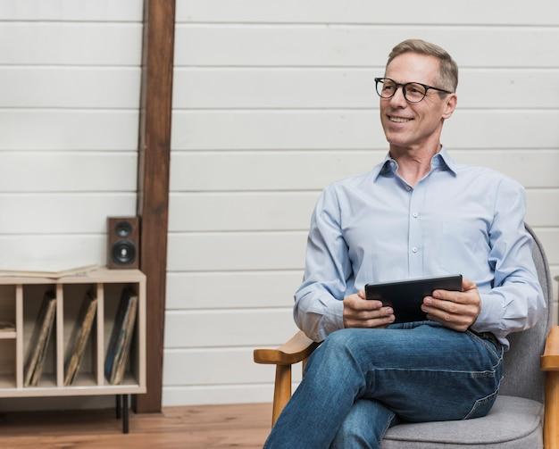 Homem maduro sorridente sentado e segurando seu tablet