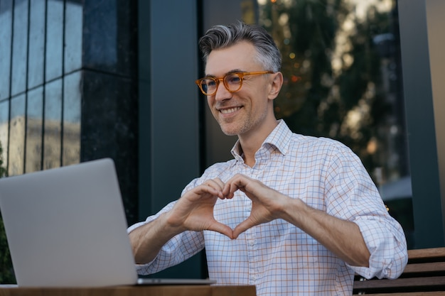 Homem maduro sorridente usando laptop, tendo vídeo-conferência. streaming de vídeo online do blogger