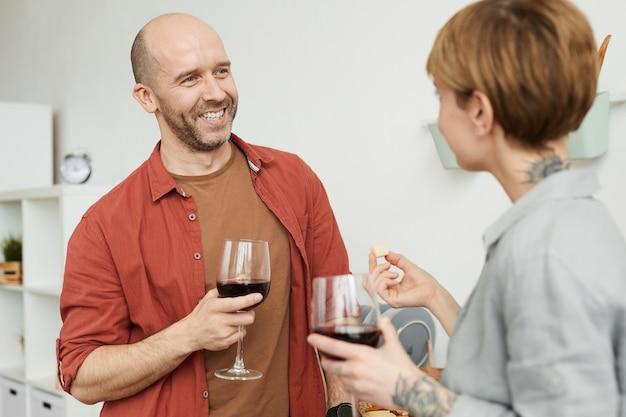 Homem maduro sorrindo e conversando com a mulher enquanto provam vinho tinto com queijo