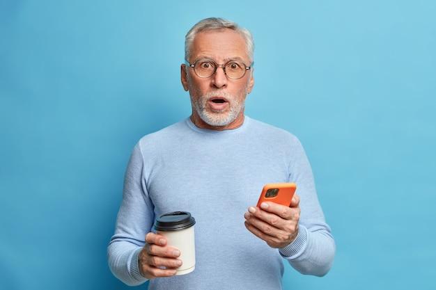 Homem maduro surpreso e animado engasga de espanto segurando um smartphone e lendo notícias, bebe café para viagem recebe notícias inesperadas usa jaqueta casual isolada sobre a parede azul
