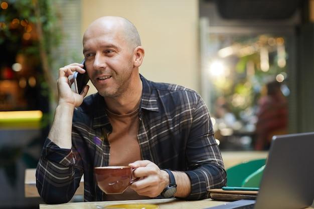 Homem maduro tomando café e falando no celular enquanto trabalha em um café