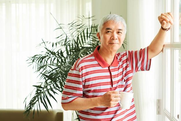Homem maduro tomando café matinal
