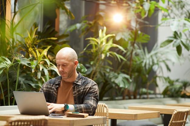 Homem maduro, trabalhando on-line, ele está sentado à mesa e digitando no laptop no café