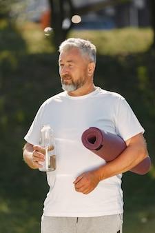 Homem maduro treinando em um parque de verão. pé sênior com um tapete. velho com uma roupa esportiva.