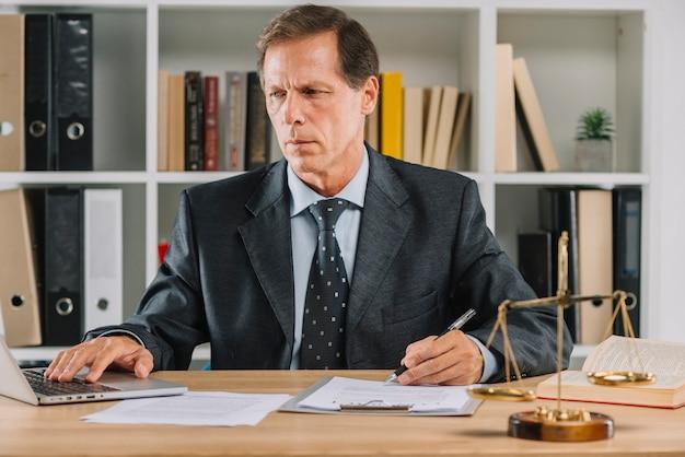 Homem maduro, usando computador portátil, enquanto, verificar, a, documento, papel, em, a, courtroom