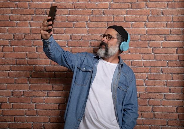 Homem maduro usando um aplicativo de smartphone com fones de ouvido. homem maduro na moda se divertindo com as novas tendências de tecnologia - conceito de tecnologia.