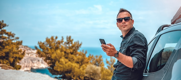 Homem magra no carro usando telefone inteligente