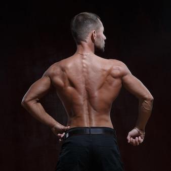 Homem magro e atlético com um torso musculoso nu isolado em uma vista de fundo escuro na parte de trás.