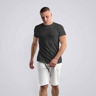 Homem magro e musculoso em uma camiseta preta e shorts cinza de malha em um fundo branco do estúdio. pose frontal. o modelo pode ser usado em seu design.