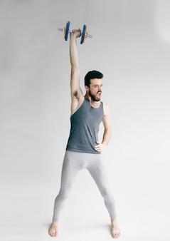 Homem magro treinando seu músculo bíceps.