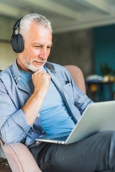 Homem mais velho com fone de ouvido preto olhando para laptop